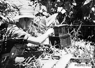 Battle of Kaiapit - An Australian soldier with an Army No. 208 Wireless Set. The large box is the radio itself; the small one is the battery. The weapon in the foreground is an Owen Gun.