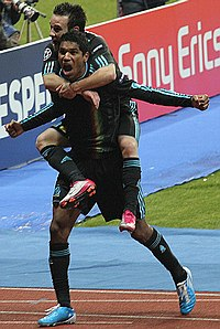 A footballer in a black kit and blue boots celebrates his goal with the cameras on the side of the pitch. A smaller teammate has jumped onto his back.