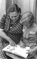 Photo en noir et blanc montrant une enfant et une femme lisant un livre