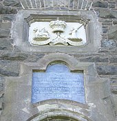 Photograph of the inscription and relief above the tower's entrance