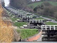 Uma série de aproximadamente 20 portões de bloqueio pretos com extremidades brancas para os braços de remo e grades de madeira, cada um ligeiramente mais alto do que o abaixo.  À direita está um caminho e em ambos os lados grama e vegetação.