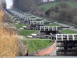 A series of approximately 20 black lock gates with white ends to the paddle arms and wooden railings, each slightly higher than the one below. On the right is a path and on both side's grass and vegetation.