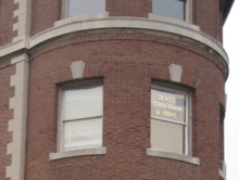 A window in a brick building showing in big letters Dewey, Cheatham & Howe