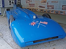 A front right view of a blue coloured racing car.