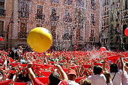 Seconds before the beginning of the San Fermín Festival in Pamplona (Spain). Town hall Square. Everybody holds his red handkerchief above his head until a firework is exploded at 12 pm; they then put it around the neck