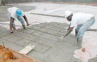 Installing rebar in a floor slab during a concrete pour