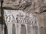 Frieze in a rock with many people.
