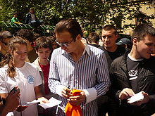 A dark-haired man in sunglasses and a wide-collared open shirt holds a pen in his hand as he looks down at a piece of paper held out to him by one of a crowd of people which surrounds him.