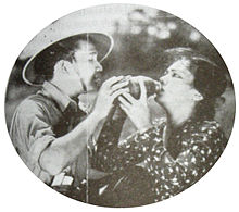 A promotional image showing a woman in a polka-dotted shirt receiving water from a man in a safari hat.
