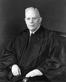A formal portrait of a judge, in his robes, sitting.