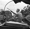 Een reisgezel van fotograaf Willem van de Poll, de heer De Haas, met een geweer…, Bestanddeelnr 252-5657.jpg