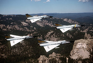 Aerospace Defense Command - Convair F-106A Delta Dart of ADC's 5th Fighter-Interceptor Squadron near Mount Rushmore (lower right background)