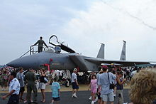 A jet sits on the tarmac while a crowd surrounds it. People are seen climbing into the jet's cockpit.