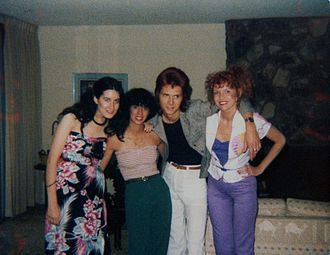 1970s in Western fashion - Group of friends in 1979. Two of the women are wearing the trendy tube tops, while the woman on the far left is wearing a rayon strapless dress