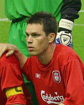 Head and upper torso of a young dark-haired white man wearing a red football shirt bearing the Carlsberg logo.