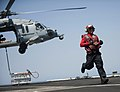 Flickr - Official U.S. Navy Imagery - A Sailor runs to clear the area after attaching crates of ordnance to a helicopter..jpg