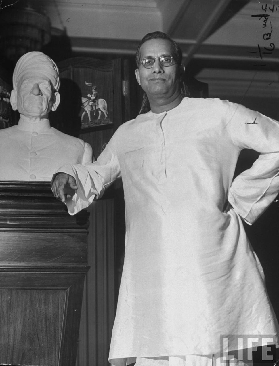 G. D. Birl, posing next to a bust of his father, at his palacial home in 1946