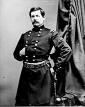 Portrait of dark-haired man with a thick mustache in an old-fashioned military uniform, standing with his hand at his hip.