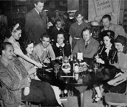 The cast of the program taking a refreshment break in January 1941. Seated, from left:Herbert Butterfield (Zeihm), Laurette Fillbrandt (Virginia Richman), John Larkin (Frankie McGinnis), Betty Winkler (Patricia Rogers), Pat Murphy (Scoop Curtis), Joan Winters (Alice Ames Warner), Frances Carlon (Ruth Lardner). Standing from left: Director Charles Urquhart, Frankie Pacelli (Jack), Henry Hunter (Scotson Webb) Girl Alone cast January 1941.jpg