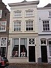 foto van Huis met schilddak en gebosseerd grijsgepleisterde lijstgevel, waarin vensters met afgeronde bovenhoeken; moderne winkelpui. Oudere achtertopgevel met vlechtingen