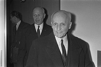 Panagiotis Pipinelis and another man, both in dark suits, walk through a doorway toward the camera