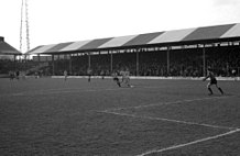 A black-and-white photograph of a football match in progress in front of a modest, single-tiered, British-style grandstand