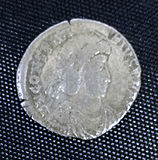 A silver coin in the centre a helmeted head surrounded by a circle of inscription with edging between that and the rim.