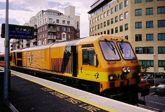 "Rail transport in Ireland - One of the 34 GM locomotives bought in the 1990s, IÉ locomotive 215 ""River Avonmore – An Abhainn Mhor"", sits at Grand Canal Dock DART station."