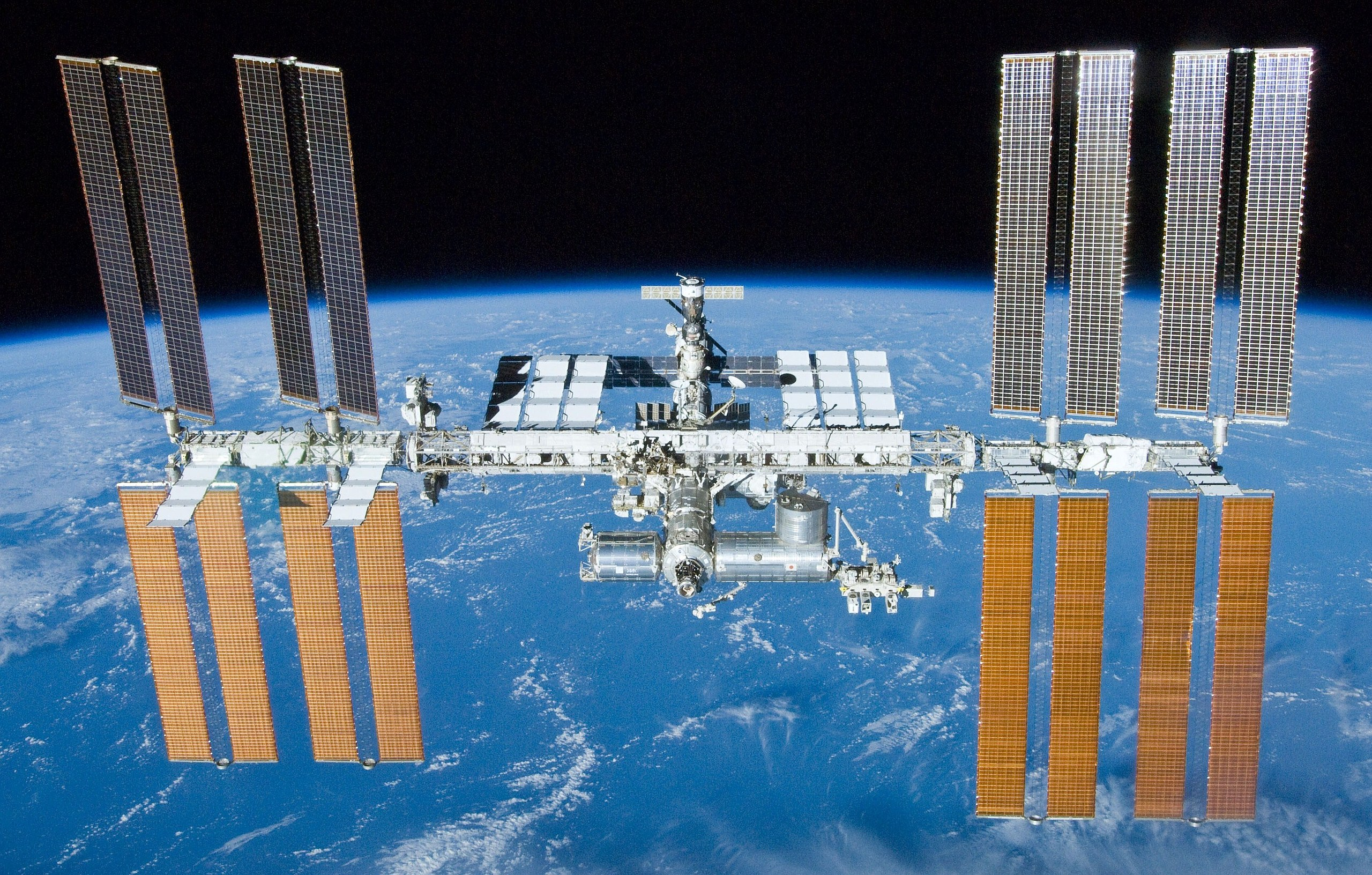 A foreward view of the International Space Station backdropped by the limb of the Earth. In view are the station's four large, maroon-coloured solar array wings, two on either side of the station, mounted to a central truss structure. Further along the truss are six large, white radiators, three next to each pair of arrays. In between the solar arrays and radiators is a cluster of pressurised modules arranged in an elongated T shape, also attached to the truss. A set of blue solar arrays are mounted to the module at the aft end of the cluster.