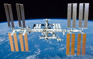 A rearward view of the ISS backdropped by the limb of the Earth. In view are the station's four large, gold-coloured solar array wings, two on either side of the station, mounted to a central truss structure. Further along the truss are six large, white radiators, three next to each pair of arrays. In between the solar arrays and radiators is a cluster of pressurised modules arranged in an elongated T shape, also attached to the truss. A set of blue solar arrays are mounted to the module at the aft end of the cluster.