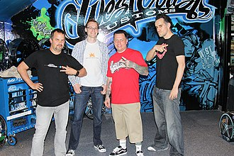 """West Coast Customs - CEO of West Coast Customs Ryan Friedlinghaus, in red, poses with three Microsoft employees. Friedlinghaus makes a """"W"""" hand sign as in the opening sequence of Inside West Coast Customs, while the Microsoft employees make V signs."""