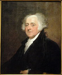 Partially bald man with white hair in black suit sits