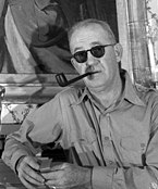 Black-an-white photograph of John Ford smoking a pipe.