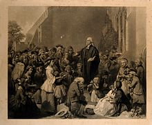 Engraving of Wesley standing on a plinth and preaching to a crowd.