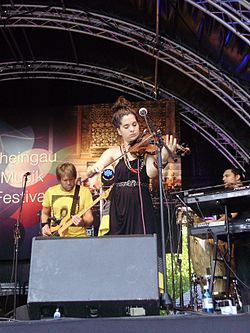 Kyla-Rose Smith playing violin onstage with Freshlyground at the Rheingau Musik Festival on 11 August 2012