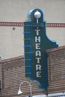 Photograph of a old theater sign on a rustic building.
