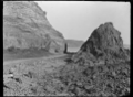 Lowry Bay Road, a narrow road between a hillside and a large rock on the foreshore. ATLIB 287905.png