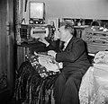 Man zittend op een bedbank terwijl hij de radio bedient, Bestanddeelnr 252-9334.jpg