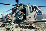 Members of a pararescue team leave an HH-3E Jolly Green Giant helicopter to begin a search and rescue mission during Exercise Patriot Coyote DF-ST-87-08133.jpg
