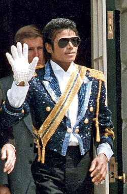 A mid-twenties Michael Jackson wearing a sequined military jacket and dark sunglasses. He is walking while waving his right hand, which is adorned with a white glove. His left hand is bare.