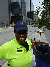 Waist high portrait of young woman wearing electric green shirt and navy blue baseball cap standing on Marquette Av downtown