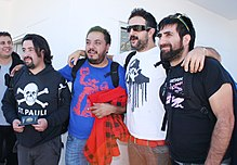 "Five people. On the extreme left one person standing with a gray shirt and black jacket. Beside a person with semi-long hair, wearing a black sweatshirt with the caption ""St. Pauli"" holding a passport in his hands. At the center a person wearing blue shirt, holding a red jacket with black boxes. At his side a person with dark glasses, beard, wearing a white shirt with a black legend and brown pants with red belt. To the far right a person standing with dark glasses on his head, bearded and wearing a black colored shirt."