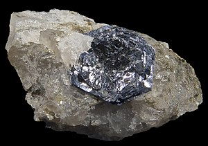 Molybdenite - Euhedral molybdenite on quartz, Molly Hill mine, Quebec, Canada. The large crystal is 15 mm across