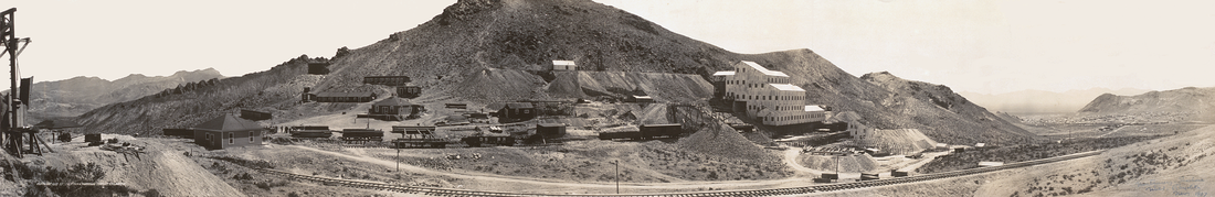 A large mill, five or six stories high and built on the side of a mountain, is surrounded by mine tailings, rail cars, piles of lumber, and a variety of smaller buildings. A rail line leads from the mining operation toward a city nestled between hills in the distance.