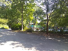 Pathway on the left with a playground seen through a group of trees