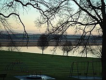 A children's play area sits amid leafless tress in the foreground. Beyond is a still body of water reflecting a cloudless sky. In the middle distance is a brown-coloured marshland, with green fields and woodlands beyond that, illuminated by a sun that is low in the sky.