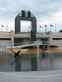 Tall arch in background, pool with statues of soldiers in foreground