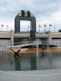 Vysoký oblouk v pozadí, bazén se sochami vojáků v popředí