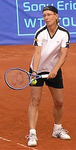 A blond-haired women with a white shirt, black shorts, and white tennis shoes on about ready to serve the tennis ball in hand
