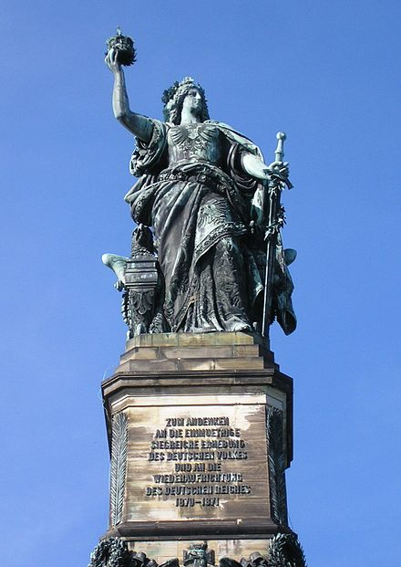 In this close-up of the Niederwald Monument (see long shot above), Germania towers 40 metres (131 ft) above the town of Rüdesheim. She holds a crown in her right hand and carries a sword at her side. The Niederwald Germania was erected 1877–1883.